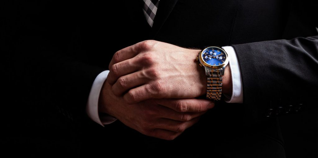 Man in suit putting on his classic watch, when searching for fine jewelry look to watch seller in Crown Point.